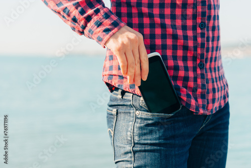 Woman takes out phone of her pocket on beach - 76971196