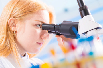 student girl looking in a microscope, science laboratory concept