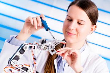 student adjusts manirulyator, the robot arm
