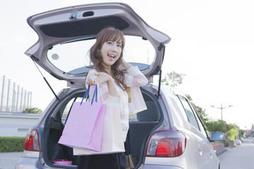 車のトランクを開けて、ショッピングバッグを持つ女性