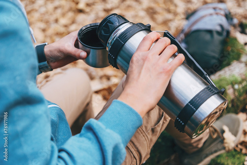 Hiker woman pours tea from thermos to cup outdoor - 76971986