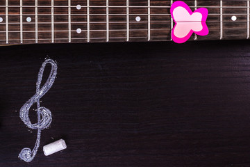 Electric guitar with treble clef on dark background