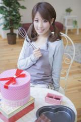 机の上にプレゼントとチョコレートを置いて泡立て器を持つ女性