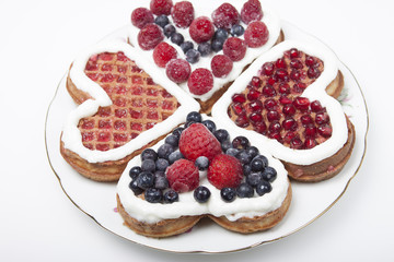 Waffle cookies in the form of hearts decorated with whipped crea