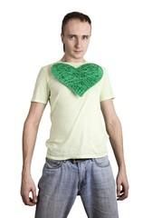 молодой мужчина держит на груди игрушечное вязанное сердце