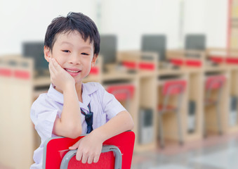 Asian student in uniform smiling in comuter room at school