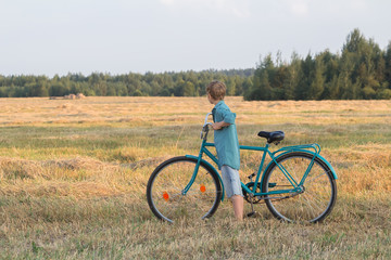 Teenager boy holding bicycle in farm field