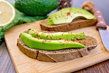 Sandwich with avocado and pepper on board