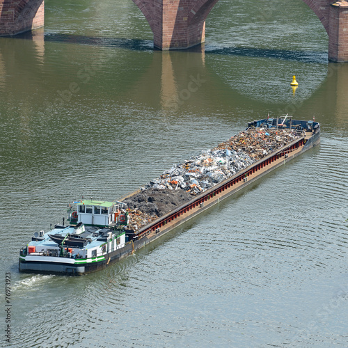 Leinwanddruck Bild Barge transports waste on the river