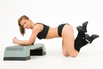 Sporty young woman does exercises on step