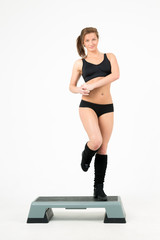 Sporty girl does exercises on step