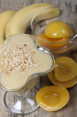 Smoothie of banana and canned peaches with nuts.