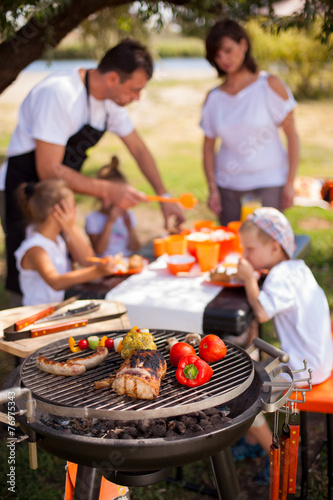 Family on vacation having barbecue - 76975343