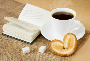 Cup of coffee with sugar, cake, spoon and book