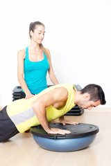 Push-ups on bosu with with female coach