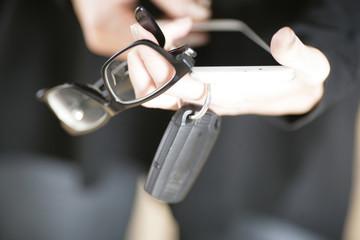 Person hält Smartphone,Brille und Schlüsselbund