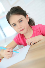 Portrait of brunette school girl writing on paper