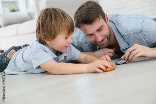 Daddy with little boy playing with toy cars - 76976127