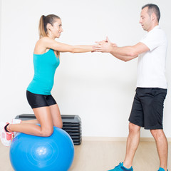 Coach helps sexy athletic woman with fitness ball exercise