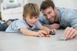 Daddy with little boy playing with toy cars - 76977115