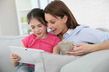 Mother with little girl websurfing on tablet