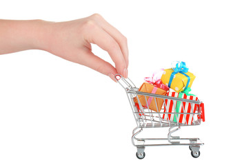 Female hand with small shopping cart full of gifts, isolated