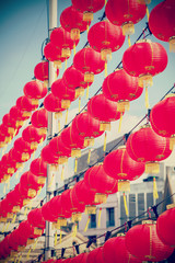 Retro filtered chinese red paper lanterns against blue sky.