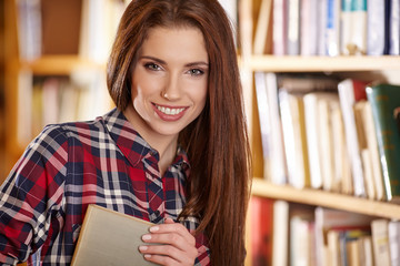 Female college student in a library (shallow DOF; color toned im