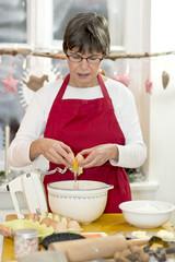 Frau mit roter Schürze backt Plätzchen in ihrer Küche