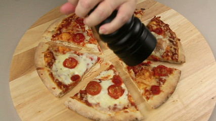 Pepper mill grinding pepper on a fresh baked pizza
