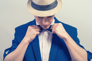 stylish guy in the hat and blue jacket dresses butterfly