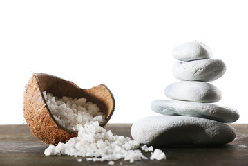 Still life of spa stones and coconut shell of sea salt