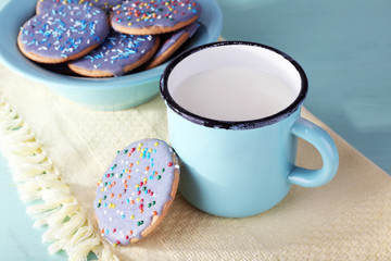Plate of glazed cookies and mug of milk