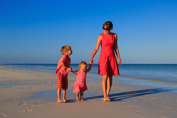mother and two kids walking on the beach