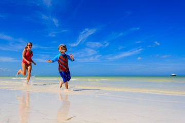 little boy and mother running on beach