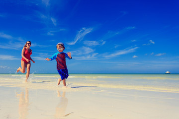 little boy and mother running on beach