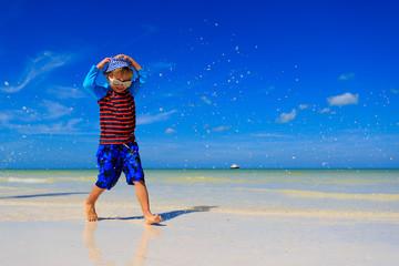 little boy splashing water on summer beach