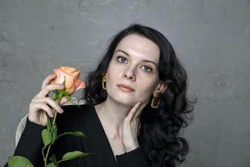 Stylish beautiful young woman with orange rose