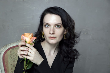 Portrait of attractive young brunette holding orange rose