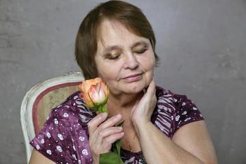 Portrait of happy elderly woman with orange rose