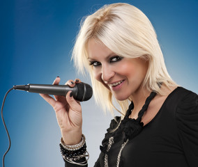 Woman singing and looking at camera on blue background