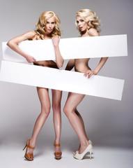 Beautiful young two women holding empty white board