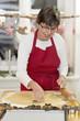 canvas print picture - Frau mit roter Schürze backt Plätzchen in ihrer Küche