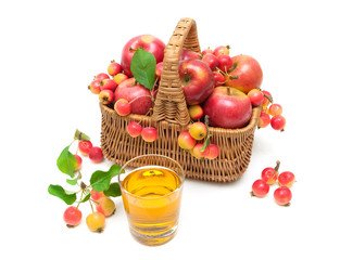 ripe apples in a wicker basket and a glass of juice isolated on