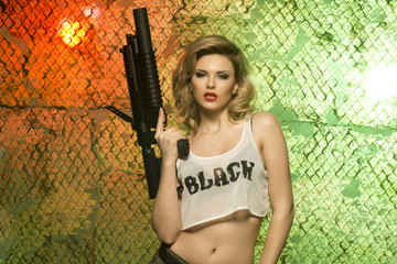 portrait of sexy blonde  with gun against camouflage net