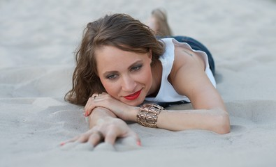 Young woman lying on the sand