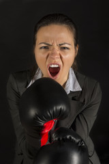 Extremely furious business woman in attack with boxing gloves