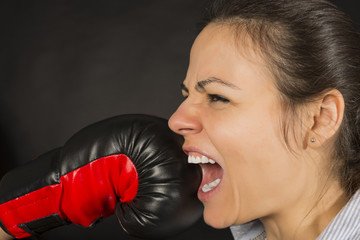 Businesswoman being punched with boxing glove in her face