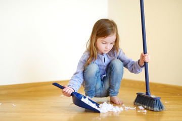 Adorable girl helping her mom to clean up