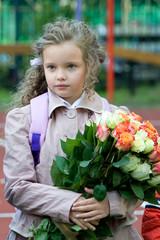 Маленькая ученица с большим букетом цветов